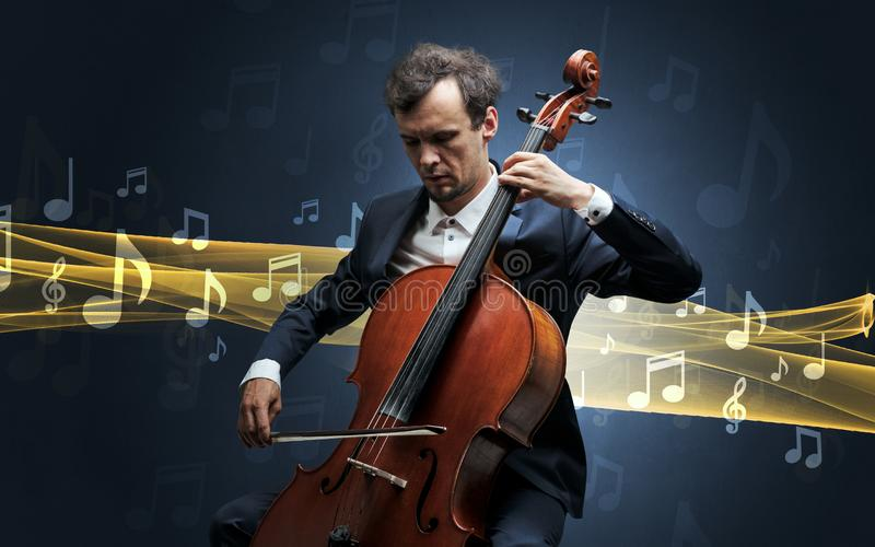 Musician playing on cello with notes around. Young male musician playing on his cello with musical notes around stock photos