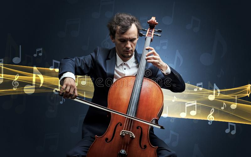 Musician playing on cello with notes around. Young male musician playing on his cello with musical notes around royalty free stock images