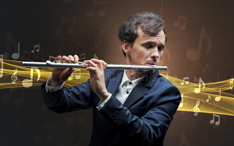 Musician playing on flute with notes around. Young male musician playing on his flute with musical notes around royalty free stock image