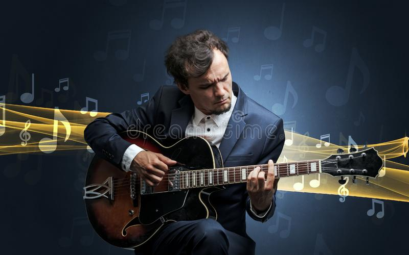 Musician playing on guitar with notes around. Young male musician playing on his guitar with musical notes around royalty free stock photo