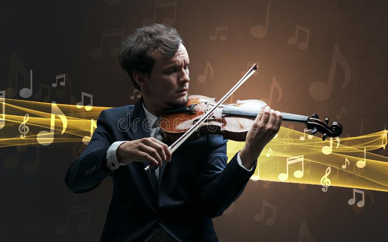 Musician playing on violin with notes around. Young male musician playing on his violin with musical notes around royalty free stock photos