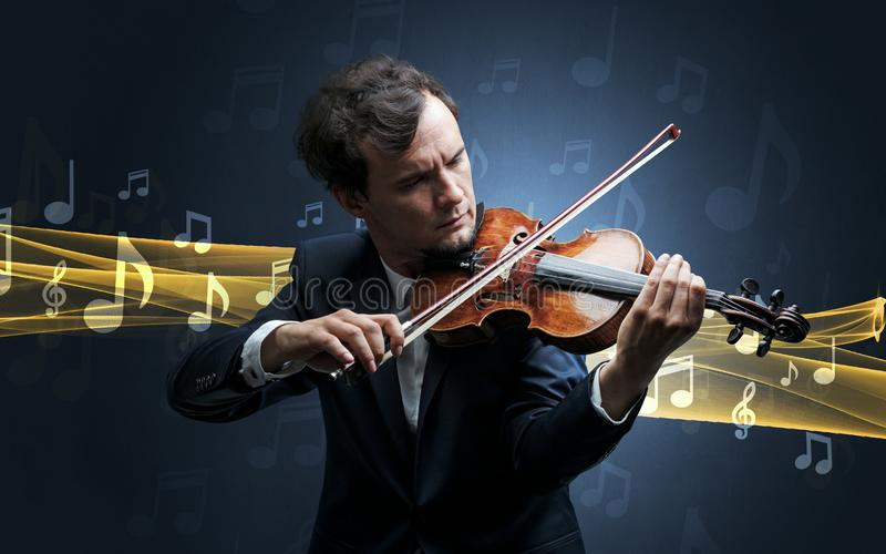 Musician playing on violin with notes around. Young male musician playing on his violin with musical notes around stock photo