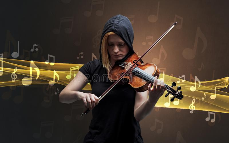 Musician playing on violin with notes around. Young male musician playing on his violin with musical notes around royalty free stock images
