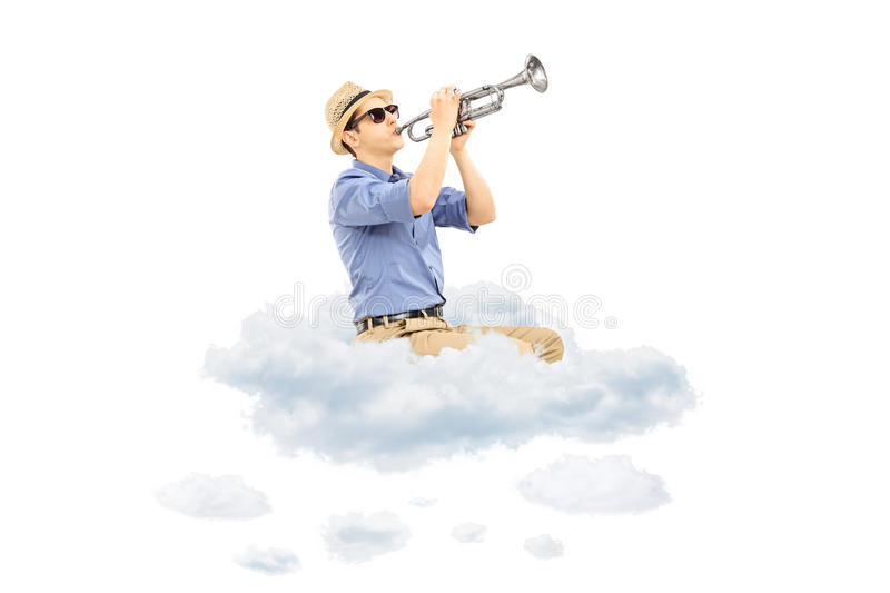 Young male musician playing a trumpet on clouds. Isolated on white background royalty free stock photography