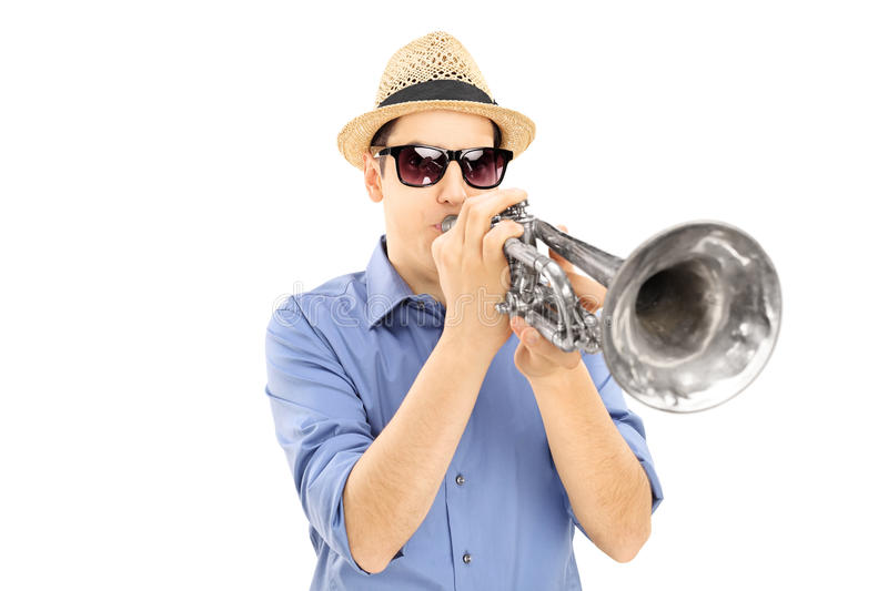 Young male musician with sunglasses blowing into trumpet. Isolated on white background stock photography