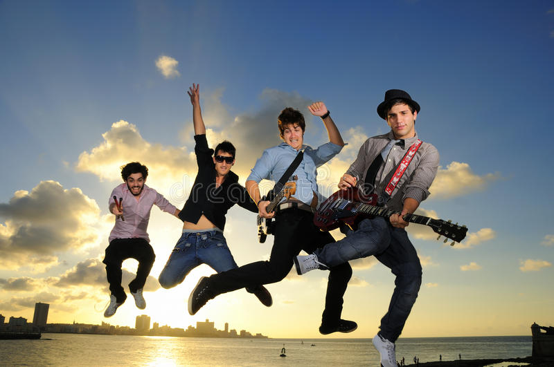 Download Young Male Musicians Jumping With Instruments Stock Photo - Image: 18659778