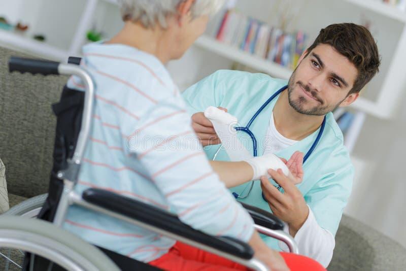 Young male nurse bandaging elderly woman`s wrist royalty free stock photography