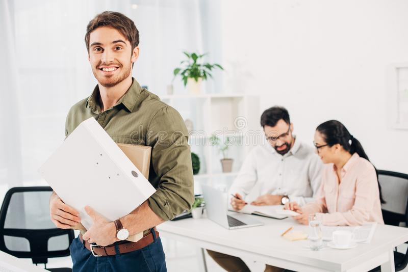 Young male office manager standing and holding folders in office with coworkers. On background stock photography