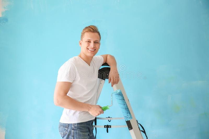 Young male painter with roller standing on ladder against color background stock photo