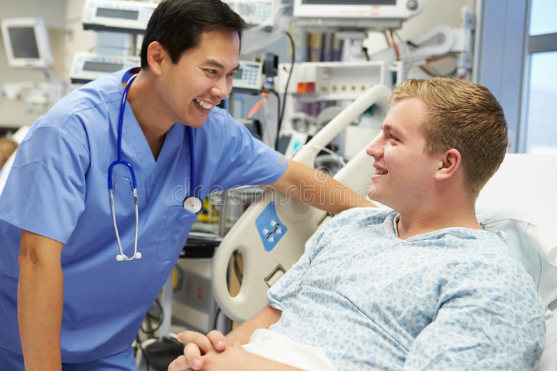 Young Male Patient Talking To Male Nurse In Emergency Room. Wearing Scrubs And Stethoscope Around Neck Smiling stock photography