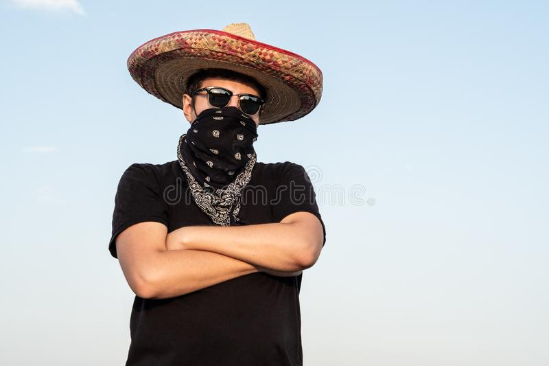 Young male person dressed up as gangster in traditional sombrero stock photo