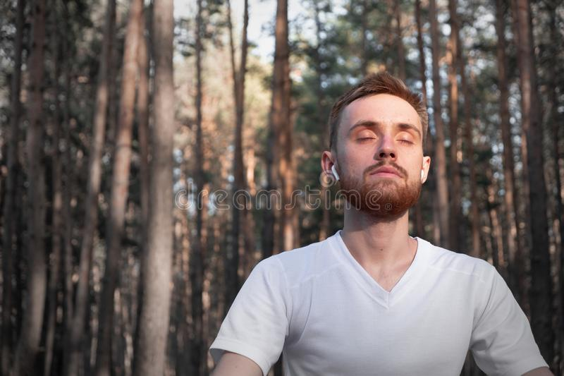 Young male person meditating in the forest using modern technology. stock photography