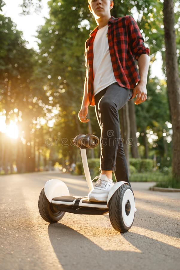 Young male person riding on gyroboard in park stock photo