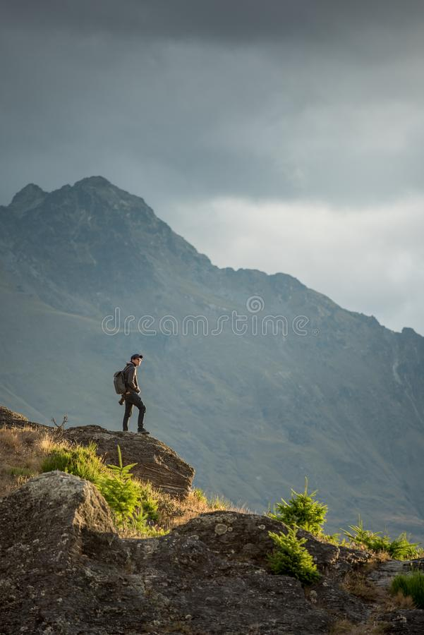 Young male photographer looking at scenery in Queenstown. Young male photographer looking at mountain scenery during golden hour sunset in Queenstown, South stock images