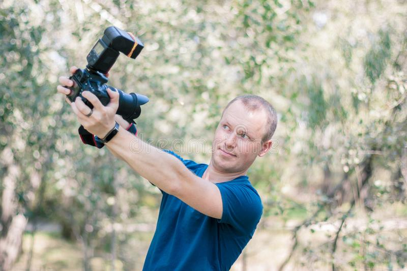 Young male photographer looks wondered to DSLR camera in his hanss on summer day. stock images