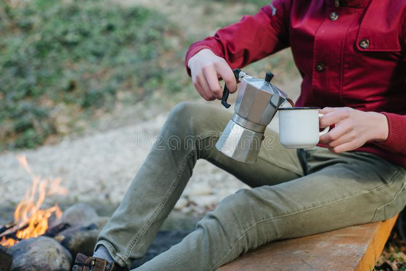 Young male pours itself hot beverage in mountains near to bonfire, relaxing after trekking. Traveler man in red jacket, sitting and holding a mug of coffee stock photography