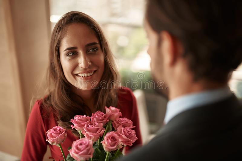 Young male presenting woman bunch of roses in cafe. Concept of romantic celebration. Waist up portrait of cheerful beautiful lady getting bouquet of flowers from royalty free stock photography