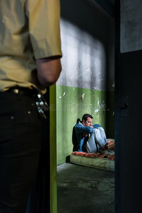 Young male prisoner sitting alone in an obsolete prison cell stock photos
