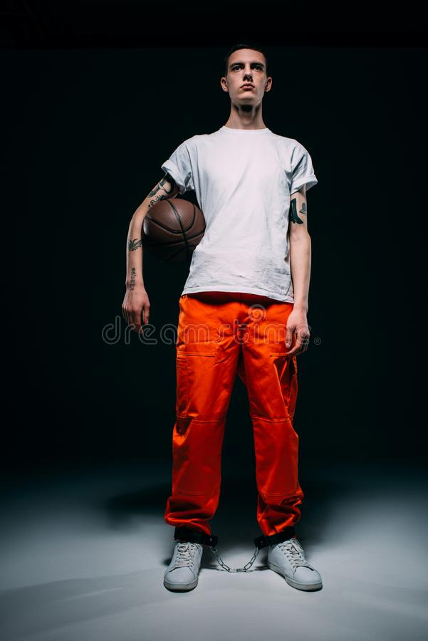 Young male prisoner wearing orange pants and cuffs holding basketball ball. On dark background royalty free stock images
