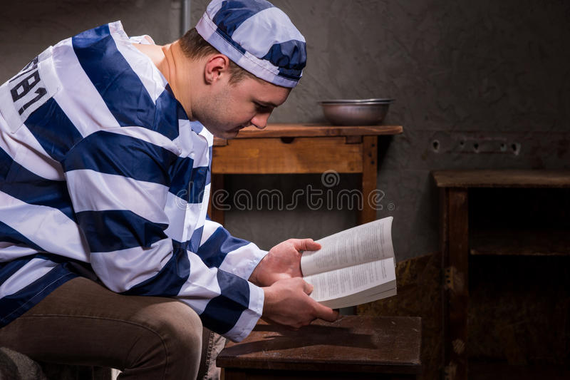 Young male prisoner wearing prison uniform reading a book or a b. Ible while sitting on a bed near bedside table with aluminum dishes in a prison cell stock photo