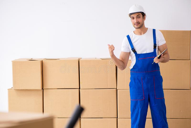 Young male professional mover doing home relocation. The young male professional mover doing home relocation stock photo