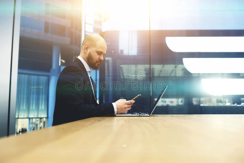 Young male proud banker checking with mobile phone the state of the currency market. Bearded businessman is calculating the income of the firm last month by royalty free stock photo