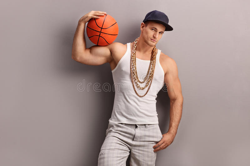 Young male rapper holding a basketball. Young male rapper with a blue cap holding a basketball and looking at the camera royalty free stock photo