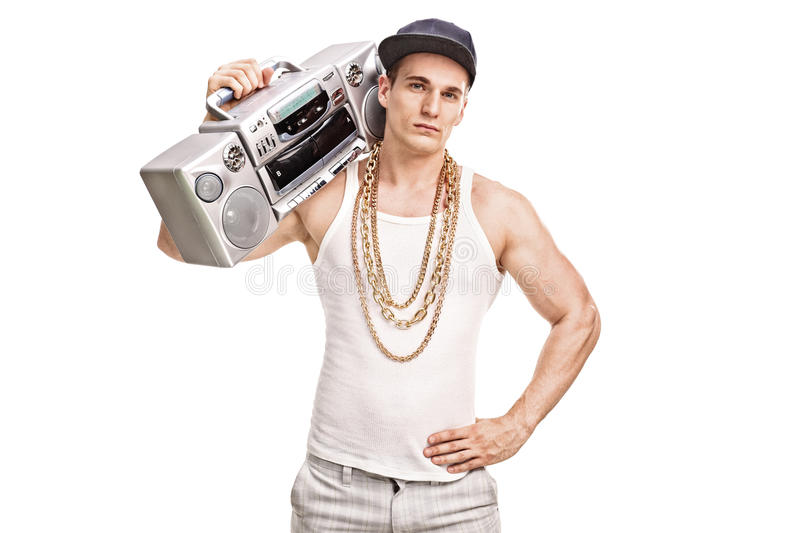 Young male rapper holding a ghetto blaster. Over his shoulder and looking at the camera isolated on white background royalty free stock image