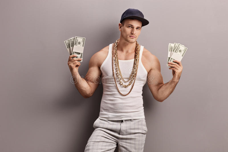 Young male rapper holding money. Young male rapper with golden chain around his neck holding few stacks of money and looking at the camera royalty free stock image