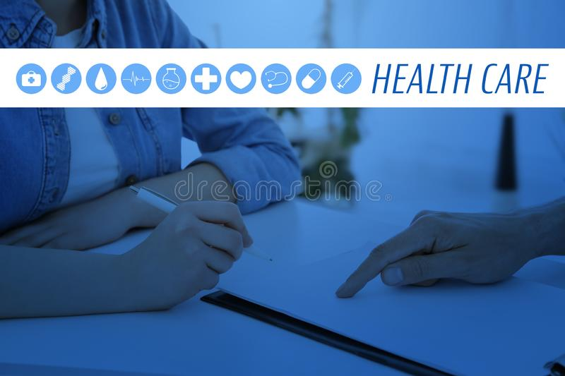 Young male receptionist working with client. In hospital stock image