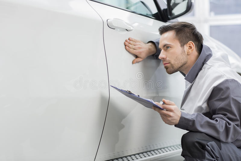 Young male repair worker examining car in automobile repair shop stock photo