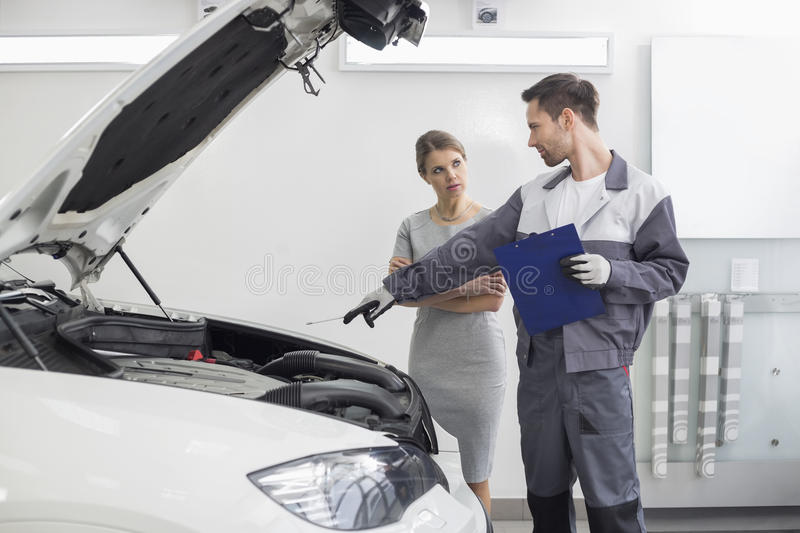 Young male repairman explaining car engine to female customer in automobile repair shop royalty free stock photo