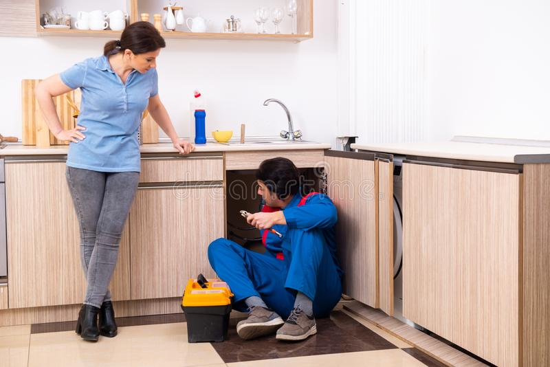 Young male repairman repairing tap. The young male repairman repairing tap royalty free stock photo