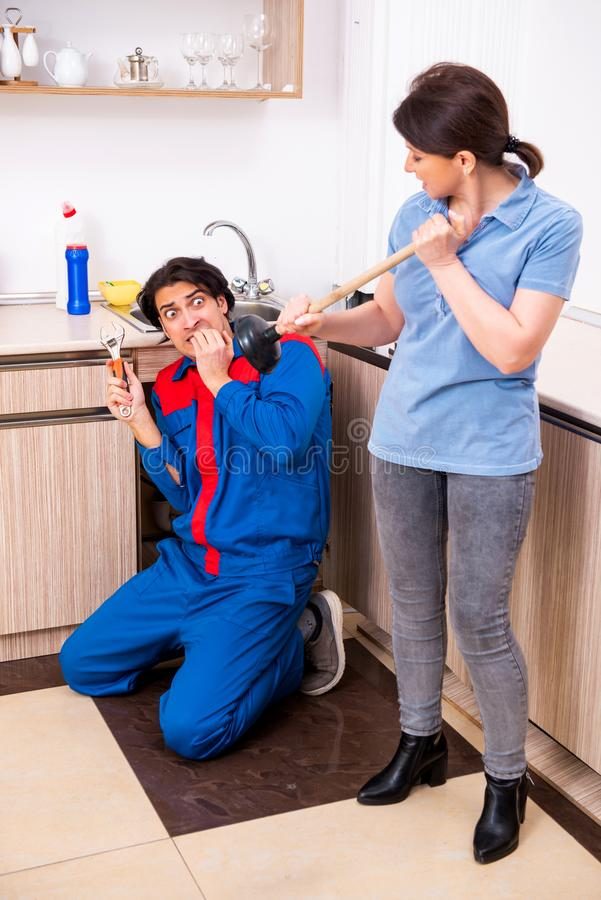 Young male repairman repairing tap. The young male repairman repairing tap royalty free stock photos