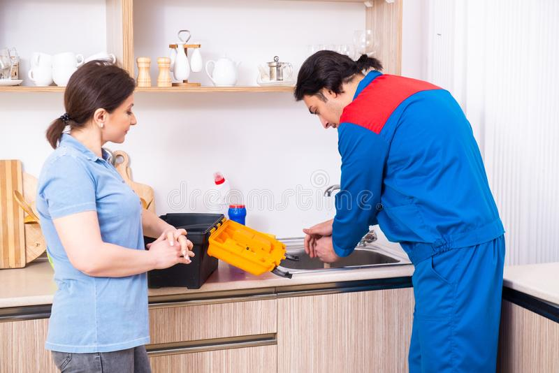 Young male repairman repairing tap. The young male repairman repairing tap stock image