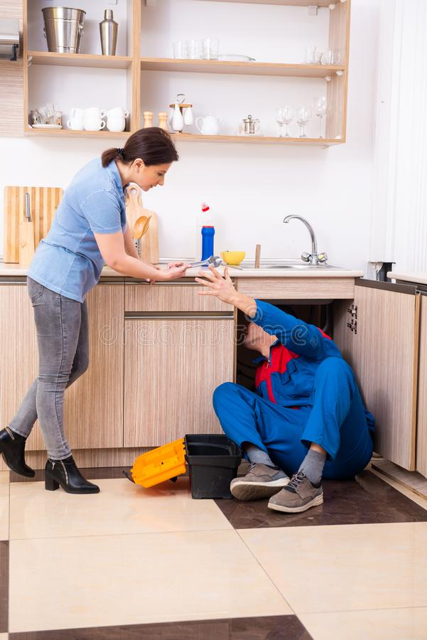 Young male repairman repairing tap. The young male repairman repairing tap royalty free stock image