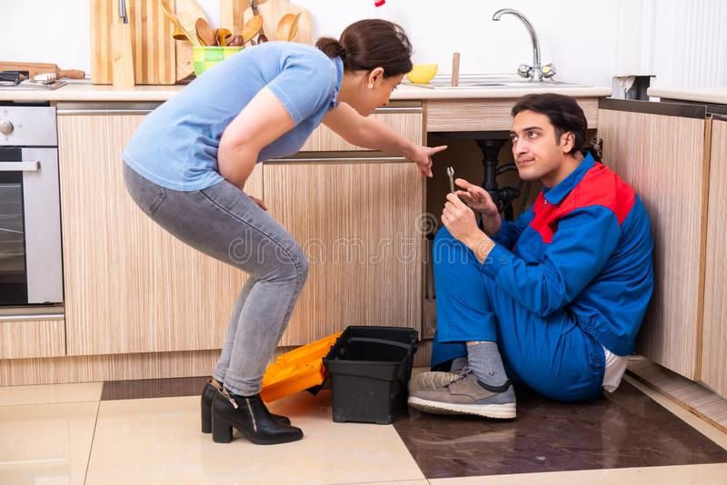 Young male repairman repairing tap. The young male repairman repairing tap stock images