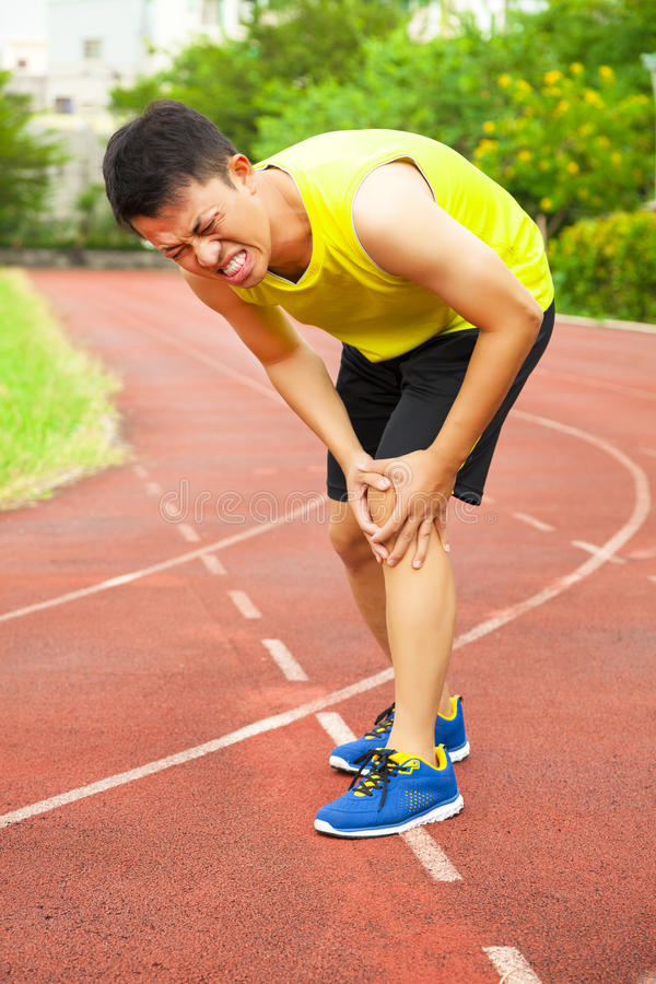 Young male runner suffering from knee injury on the track. In the stadium stock photography