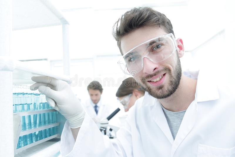 Young male scientist looking at a sample in a test tube side vie stock photos