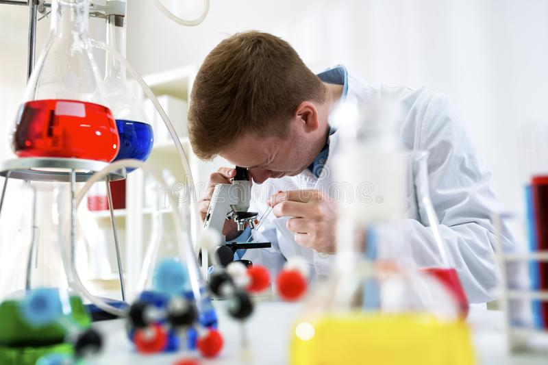 Young scientist working with microscope at the clinic laboratory stock photo