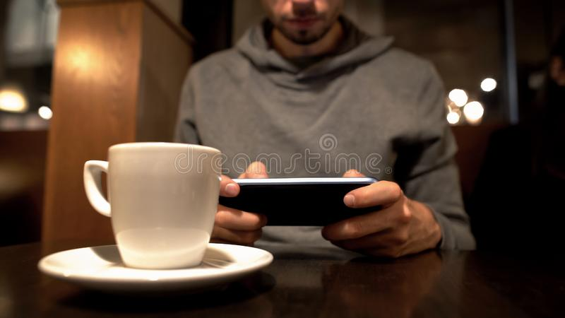 Young male scrolling smartphone in cafe, surfing internet, gadget addiction. Stock photo royalty free stock images
