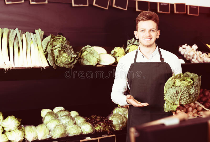 Young male seller offering cabbage stock image