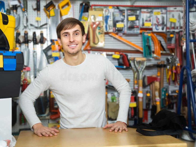 Young male seller posing at tooling section royalty free stock photo