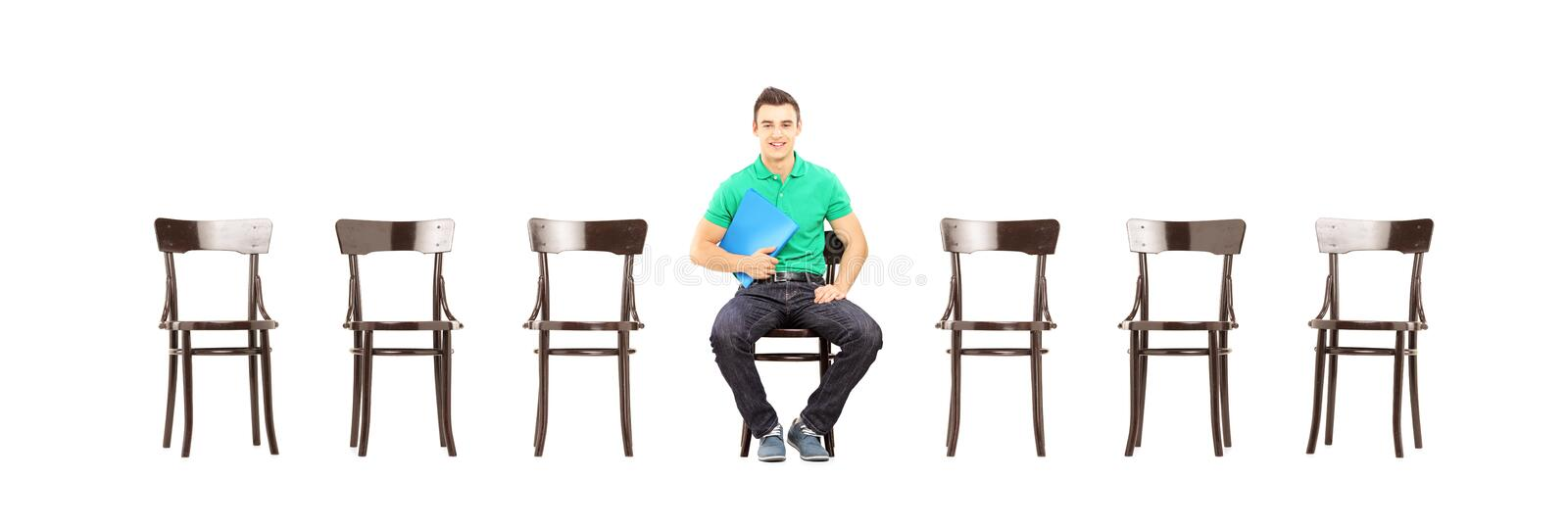 Young male sitting on a chair and waiting for job interview royalty free stock image