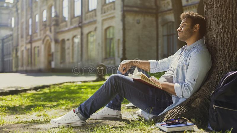 Young male sitting under tree with book looking around, having pleasant thoughts stock photography