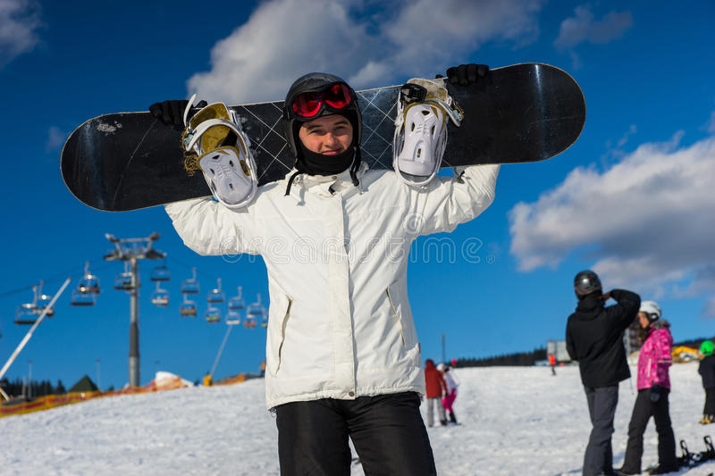 Young male in ski-suit standing and holding his snowboard on his. Young male in ski-suit, helmet and ski goggles standing and holding his snowboard on his stock photos