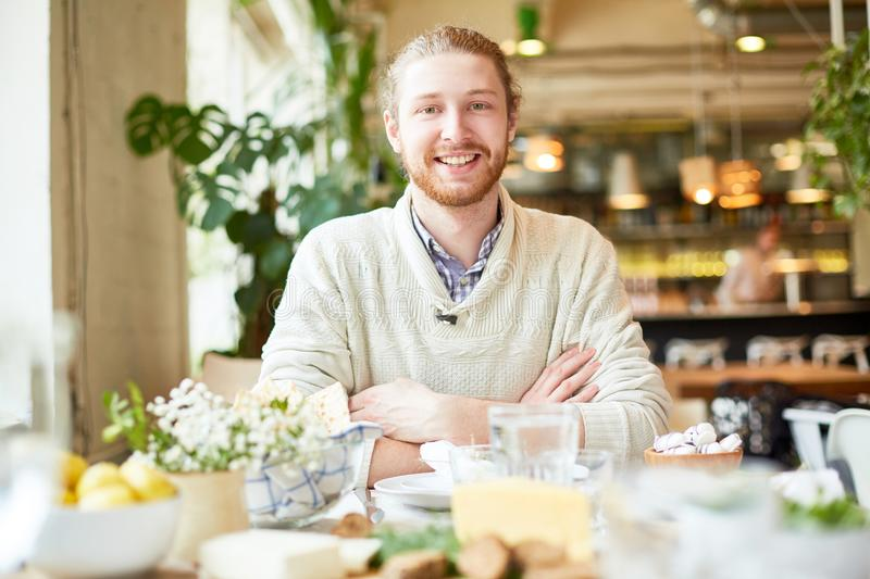 Young male smiling and looking at camera in cafe royalty free stock photo