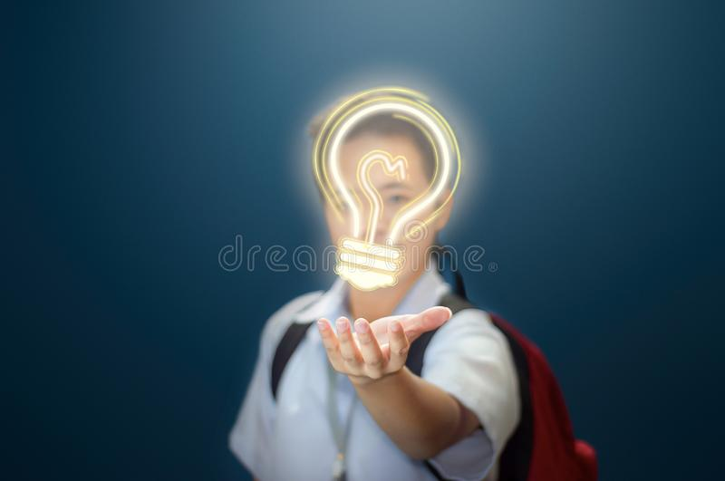 Young male student holding a light bulb bringing a brilliant idea. stock photography