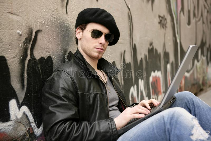Young male student sit laptop silver graffiti royalty free stock photos