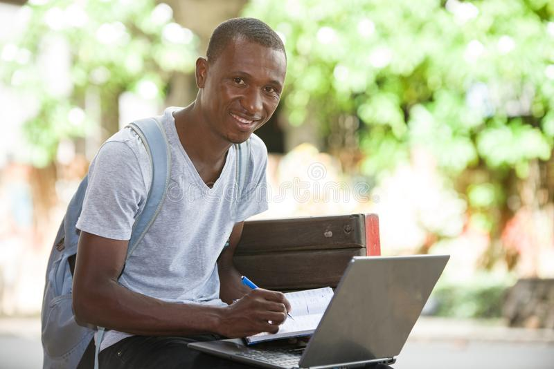 Young male student sitting in city working with laptop and notebook. Young attractive student man in the city working with laptop looking for satisfaction and stock photo
